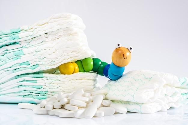 Enterobíase é uma infecção de vermes, verme de brinquedo com algumas fraldas e pílulas.