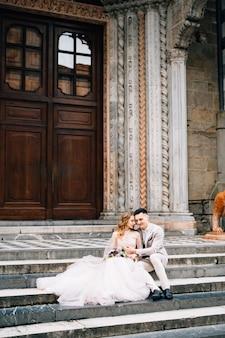 Entrada da basílica de santa maria maggiore, em roma, recém-casados sentados nos degraus se abraçando