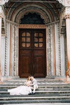 Entrada da basílica de santa maria maggiore roma recém-casados sentados nos degraus se abraçando