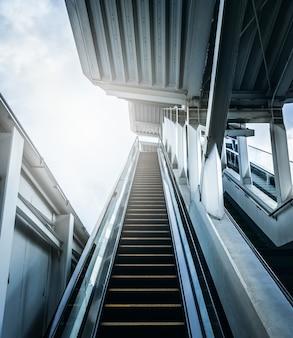Entrada da escada rolante na estação de metro com luz solar. conceitos futuros.