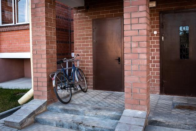 Entrada de prédio de apartamentos com porta metálica com interfone.