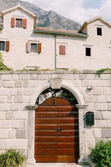 Entrada para o pátio por uma porta de metal fechada com elementos de ferro forjado no arco