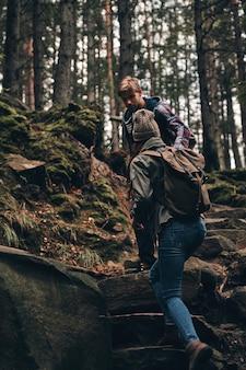 Entrar em contato com a natureza. jovem casal de mãos dadas e subindo durante uma caminhada na floresta