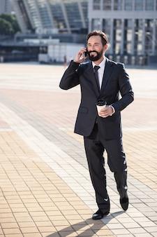 Entrar em contato. homem de negócios alegre caminhando para o trabalho enquanto conversa ao telefone