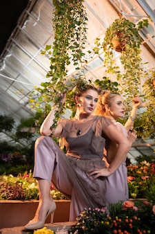 Entre as plantas. mulheres bonitas e atraentes tocando uma planta verde enquanto estão embaixo de um vaso de flores