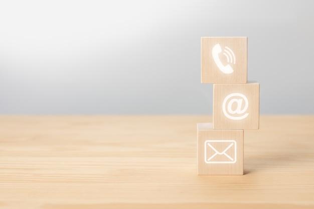 Entre em contato conosco por ícone de telefone, e-mail, correio em cubo de madeira, atendimento ao cliente e suporte. cubos de madeira com símbolo de telefone, e-mail, endereço. copie o espaço