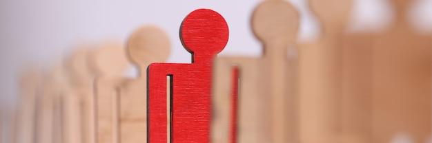 Entre o grupo de homens de brinquedo de madeira, há um close up vermelho
