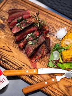 Entrecosto de carne carne de bife grelhada com chamas de fogo na tábua de corte de madeira com ramo de alecrim, pimenta e sal. legumes grelhados, milho. chef master cozinhando um delicioso churrasco.