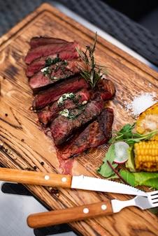 Entrecosto de carne grelhada na brasa com ramo de alecrim e legumes grelhados de milho na madeira