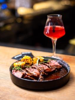 Entrecosto de carne grelhada na brasa com ramo de alecrim e vegetais grelhados