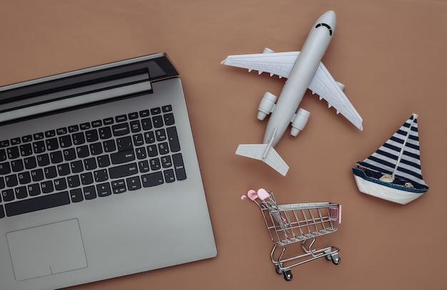 Entrega, compras online. laptop e veleiro, carrinho de compras, avião de ar em fundo marrom. vista do topo. postura plana