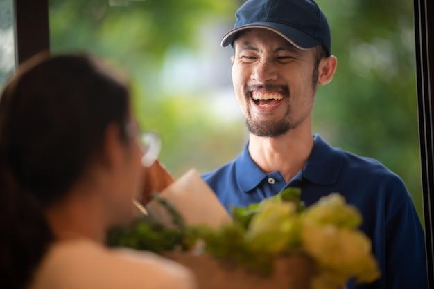 Entrega de alimentos e conceito de serviço de courier, a equipe de entrega de uniforme está atualmente trabalhando para entregar alimentos e produtos frescos na casa do cliente