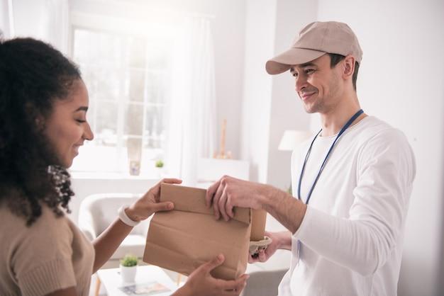 Entrega de alimentos. pessoa simpática e feliz pegando a sacola enquanto olha para o entregador