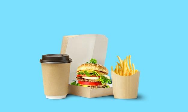 Entrega de almoço de fast food. saboroso hambúrguer, batatas fritas e café em embalagem de papelão sobre fundo azul.