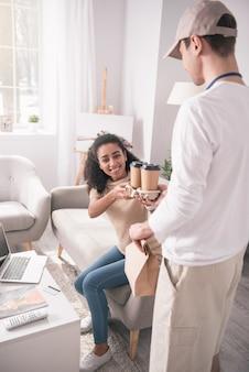 Entrega de café. mulher simpática e encantada sentada no sofá enquanto toma café do entregador