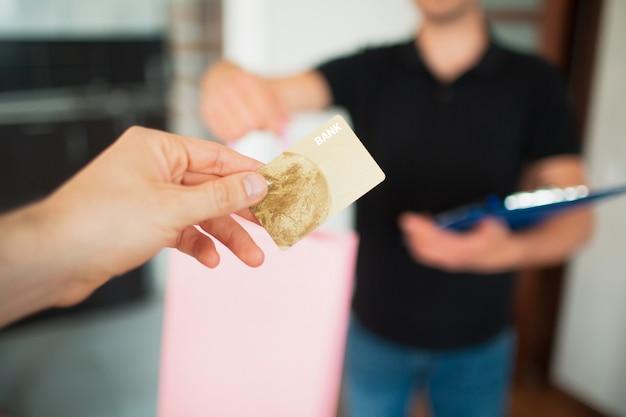 Entrega de coisas ou bens para casa. close-up de um cartão de crédito contra a parede de um mensageiro ou entregador