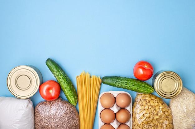 Entrega de comida. arroz, trigo sarraceno, macarrão, comida enlatada, açúcar sobre fundo azul.