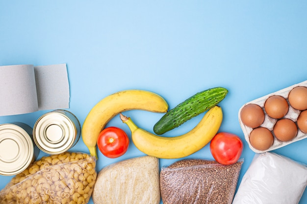 Entrega de comida. arroz, trigo sarraceno, macarrão, conservas, açúcar, papel higiênico sobre fundo azul.