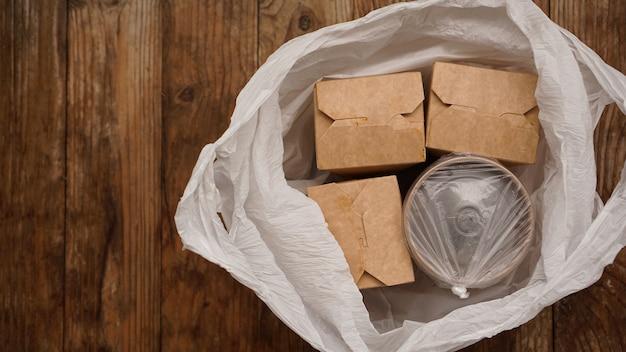 Entrega de comida asiática. alimentos em recipientes e em um pacote sobre um fundo de madeira. embalagem de comida japonesa e sushi.