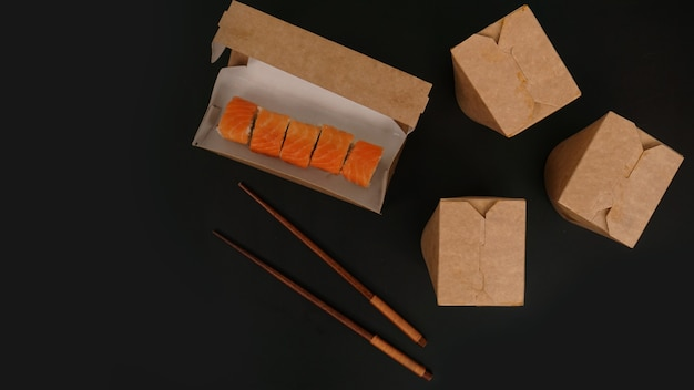 Entrega de comida asiática. embalagem para sushi e woks. alimentos em embalagens de papel em fundo preto. embalagem aberta com rolinhos de salmão