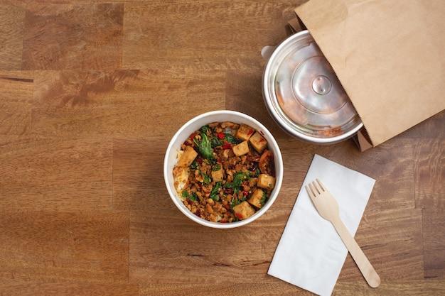 Entrega de comida asiática para viagem na mesa de madeira