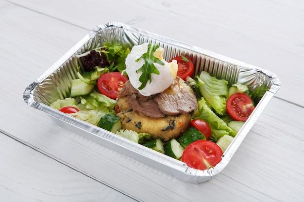 Entrega de comida de restaurante em caixa de papel alumínio na mesa de madeira branca. close up de ovo escalfado em bife de véu malpassado com salada de legumes fresca e almofada de cuscuz. o prato tira o close up, a refeição saudável.