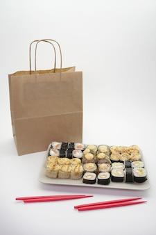 Entrega de comida japonesa, conjunto de sushi e pacote de artesanato em um fundo isolado