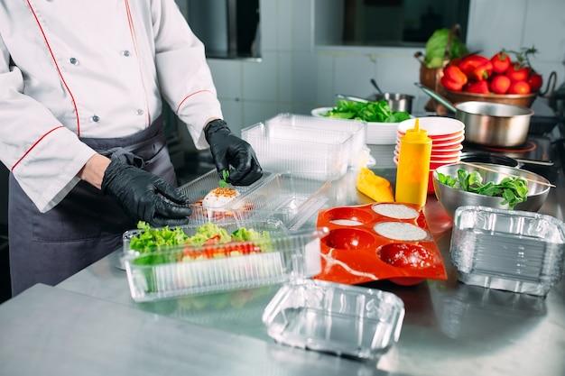 Entrega de comida no restaurante. o chef prepara a comida no restaurante e a embala em pratos descartáveis.