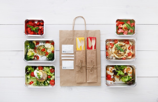 Entrega de comida saudável. tire a comida. salada de legumes, carne e frutos silvestres em caixas de papel alumínio, talheres e embalagem de papel pardo. vista superior, camada plana em madeira branca