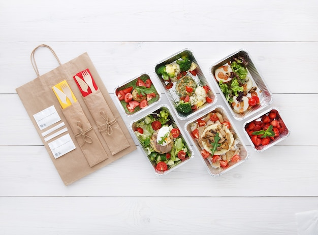 Entrega de comida saudável. tire a comida. vegetais, salada de carnes e frutos silvestres em caixas de alumínio, talheres, água e embalagem de papel pardo. vista superior, camada plana em madeira branca com espaço de cópia
