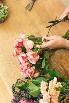 Entrega de flores, criação de pedido. cortes de mãos de florista rosa para buquê na loja de flores.