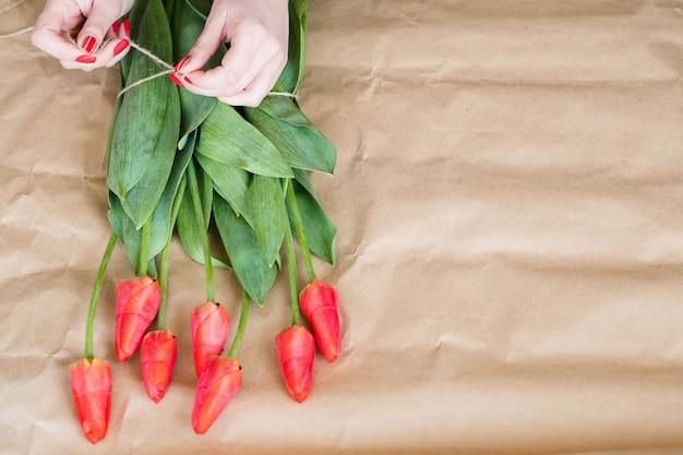 Entrega de flores. florista organizando um buquê de tulipa vermelha. mãos de mulher amarrar um laço de barbante.