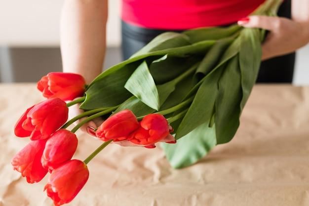 Entrega de flores. florista segurando um buquê de tulipa vermelha. grupo festivo da primavera