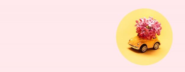 Entrega de flores frescas para o feriado. carro de brinquedo amarelo com ramo de flor lilás.