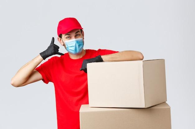 Entrega de pacotes e encomendas, quarentena covid-19 e ordens de transferência. correio amigável com uniforme vermelho, máscara facial e luvas, pedindo ao cliente que ligue, mostre o sinal do telefone, fique perto das caixas.