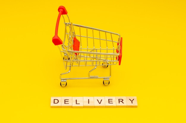 Entrega de palavras feita de cubos de madeira em fundo amarelo com carrinho de compras de brinquedos