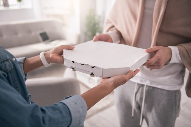 Entrega de pizza. close de uma caixa com pizza sendo levada por um homem simpático e faminto