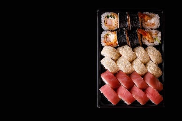 Entrega de sushi. conjunto de rolos em uma caixa descartável em um fundo preto. vista do topo