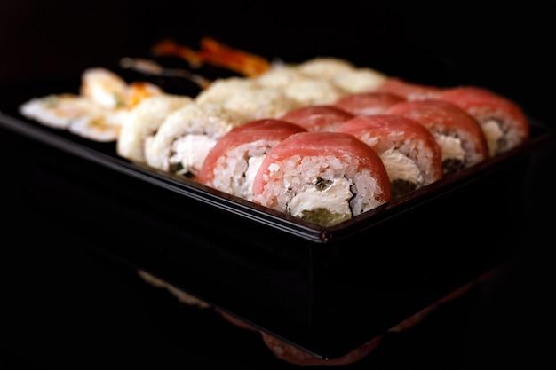 Entrega de sushi. conjunto de rolos em uma caixa descartável em uma superfície preta.