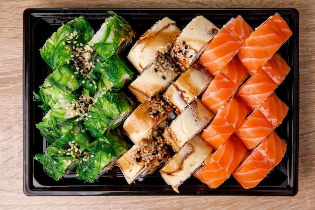 Entrega de sushi. diferentes rolos em embalagem plástica preta. vista superior compondo. comida japonesa e asiática.