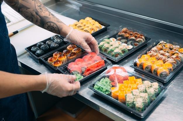 Entrega de sushi. muitas variedades de sushi em uma caixa de plástico são preparadas para entrega.