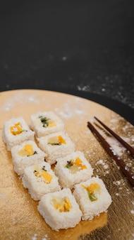 Entrega de sushi. rolinhos doces feitos de arroz, abacaxi, kiwi e manga. rolos em um fundo dourado e preto. palitos de madeira para sushi.