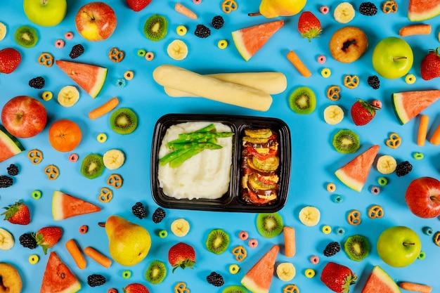 Entrega do almoço em um recipiente de plástico purê de batatas com aspargos e legumes.