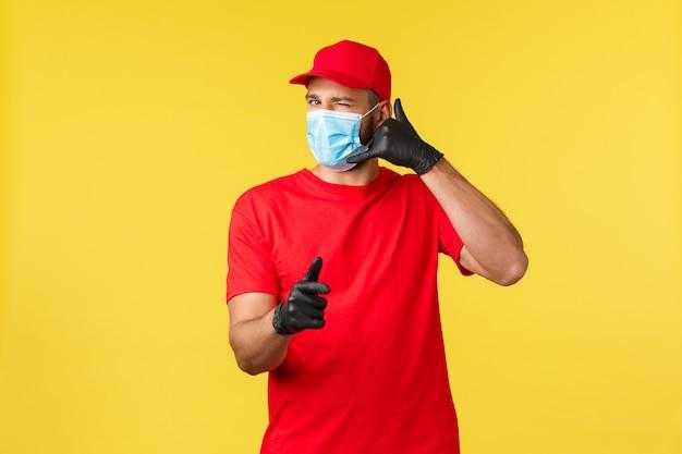 Entrega expressa durante a pandemia, covid-19, frete seguro, conceito de compra online. correio amigável em uniforme vermelho, máscara médica e luvas, serviço de piscar e pedir chamada, câmera apontando