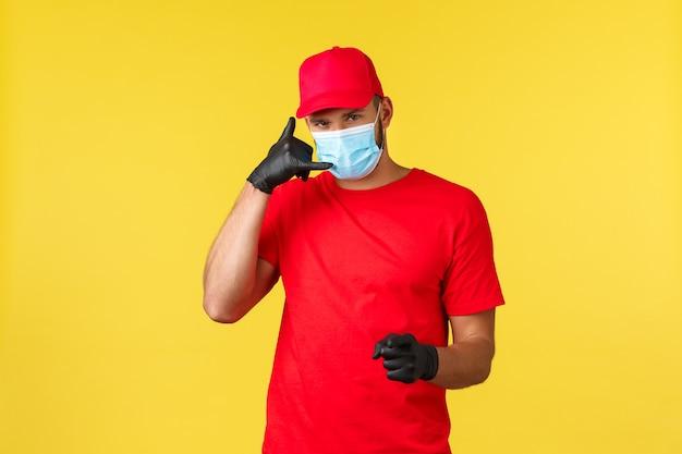 Entrega expressa durante a pandemia, covid-19, frete seguro, conceito de compra online. mensageiro bonito em uniforme vermelho e máscara médica pede aos clientes que liguem, entreguem pacotes em todo o mundo, forneça segurança