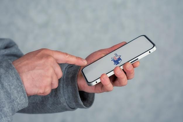 Entrega expressa em seu telefone. um homem tem nas mãos um smartphone com um ícone em uma tela branca.