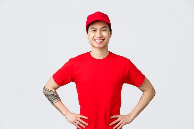 Entrega expressa, transporte e conceito de logística. correio asiático confiante alegre com boné vermelho e camiseta, entusiasmado com as mãos nos quadris, sorrindo, entregando o pedido ao cliente a tempo.