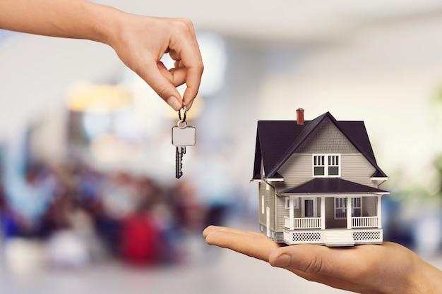 Entrega manual de chaves de metal e mini casa
