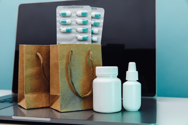 Entrega online e conceito de compras. sacos de papel com medicamentos e comprimidos controlados e contêineres brancos no laptop.