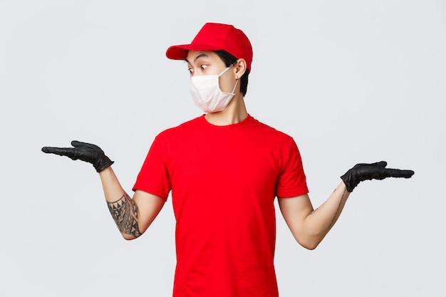 Entrega pandêmica covid-19, conceito de transportadoras. correio asiático surpreso em uniforme vermelho, luvas de proteção e máscara médica, segurando duas ofertas promocionais nas mãos, olhando chocado na palma da mão com o item